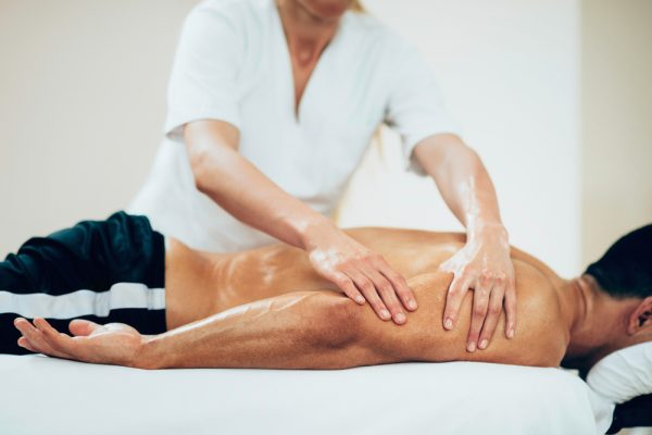 sports massage therapist massaging athlete