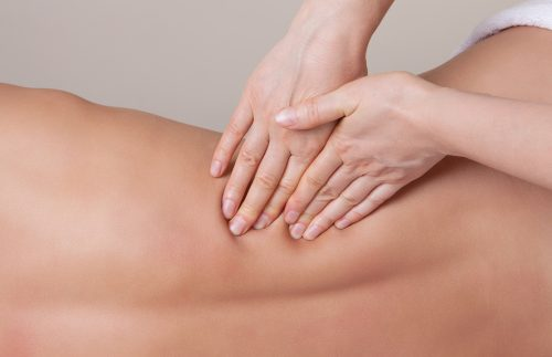 massage therapists hands on back