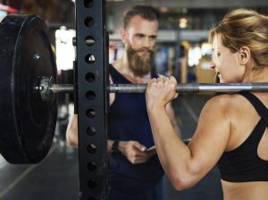 girl doing squats with a trainer