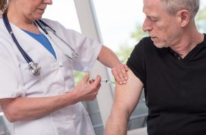 female doctor vaccinating a senior man
